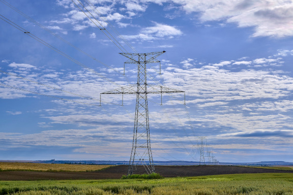 Strommasten auf grünem Feld und blauen Himmel